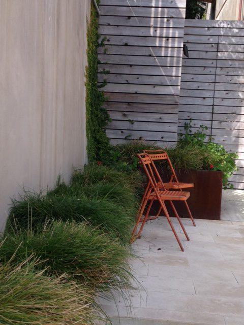 red metal garden chairs near corten steel planters