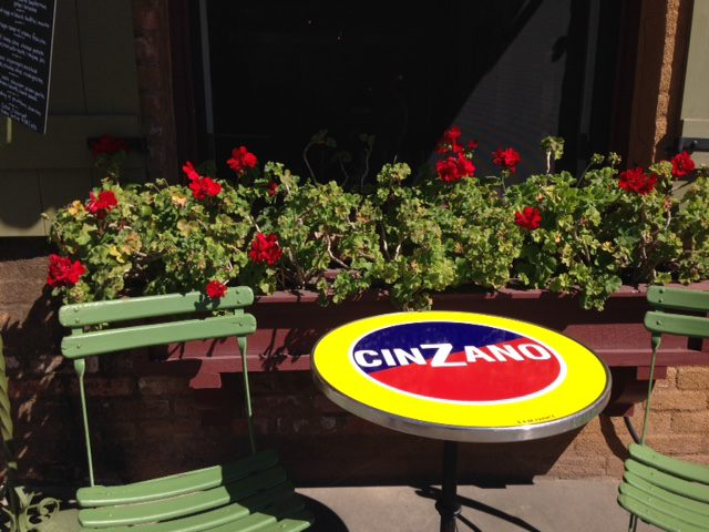 red flowering geraniums and bistro table